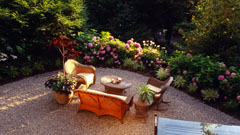 Pebble patio with outdoor furniture and flower gardens